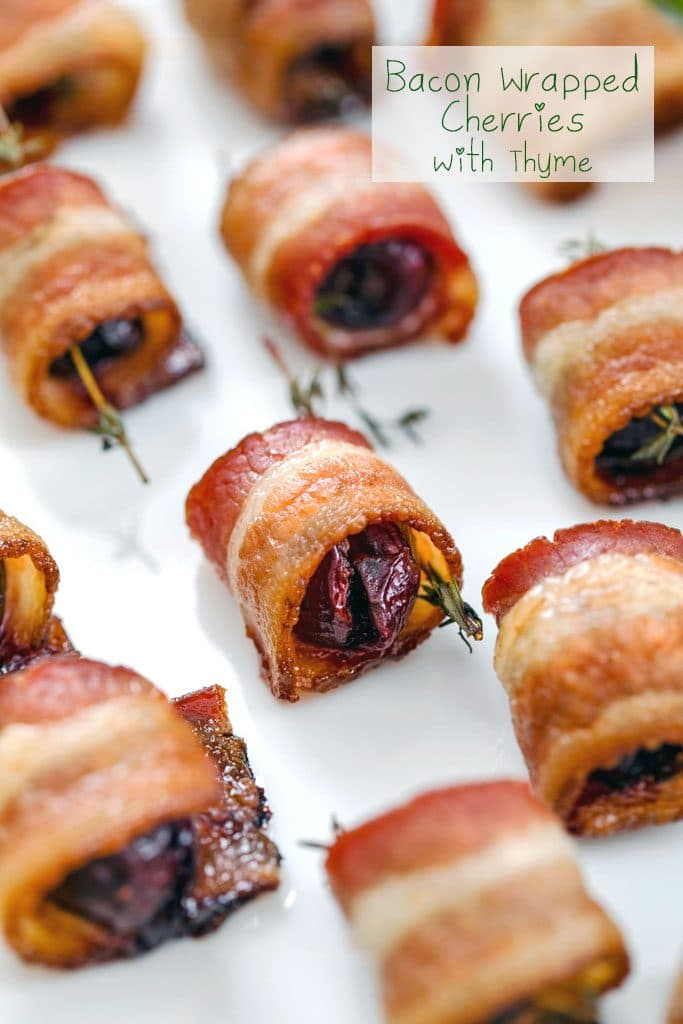 "Close-up of platter of bacon wrapped cherries with thyme on white plate with ""Bacon Wrapped Cherries with Thyme"" text at top"