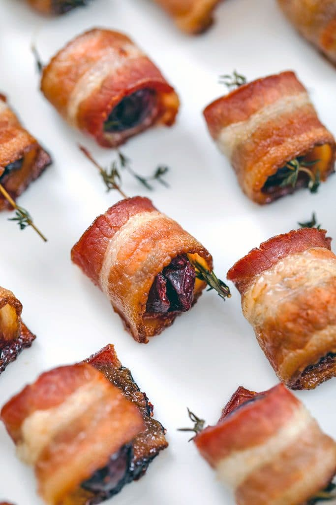 Close-up of bacon wrapped cherries with thyme after baking on white plate