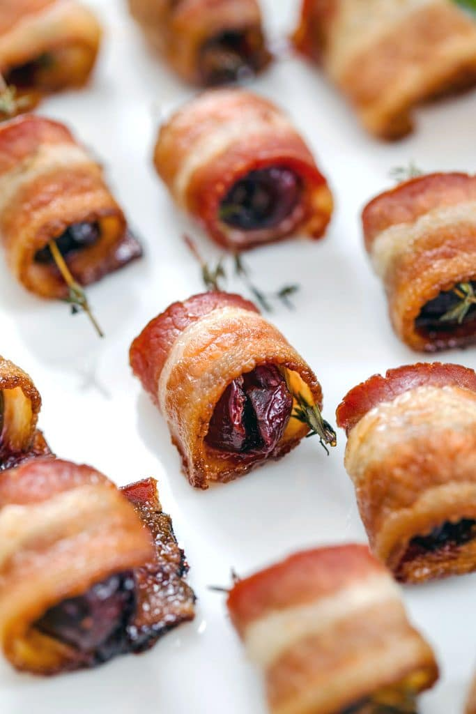 Close-up of platter of bacon wrapped cherries with thyme on white plate