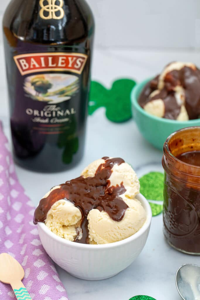 Overhead view of bowl of Baileys ice cream with Baileys hot fudge sauce with jar of fudge sauce, bottle of Baileys Irish Cream, and second bowl of ice cream in background