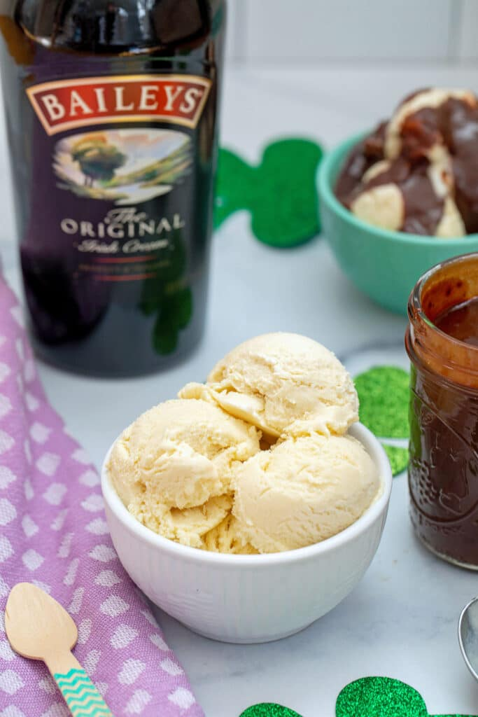 Head-on view of a bowl of Baileys ice cream with bottle of Baileys, jar of chocolate fudge sauce, and second bowl of ice cream in background
