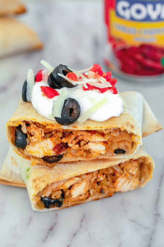 Head-on view of a baked chicken chimichanga cut in half on a marble surface and topped with sour cream, tomatoes, cheese, and olives, with can of chipotle peppers in background