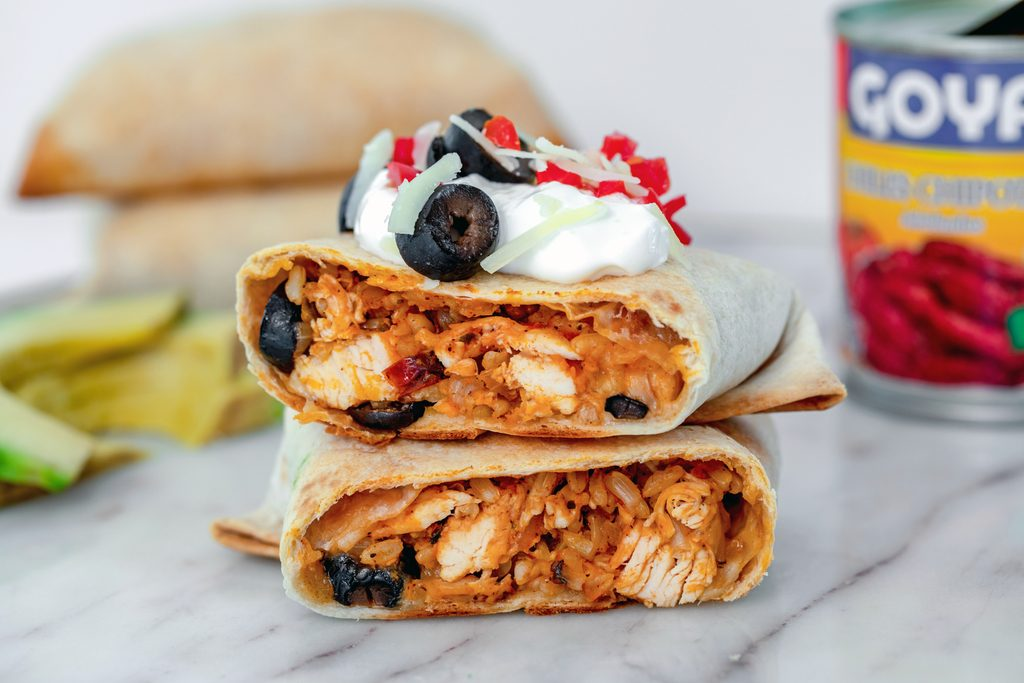 Landscape head-on view of baked chicken chimichanga cut in half and topped with sour cream, shredded cheese, olives, and tomatoes with sliced avocado, can of chipotle peppers, and more chimichangas in the background