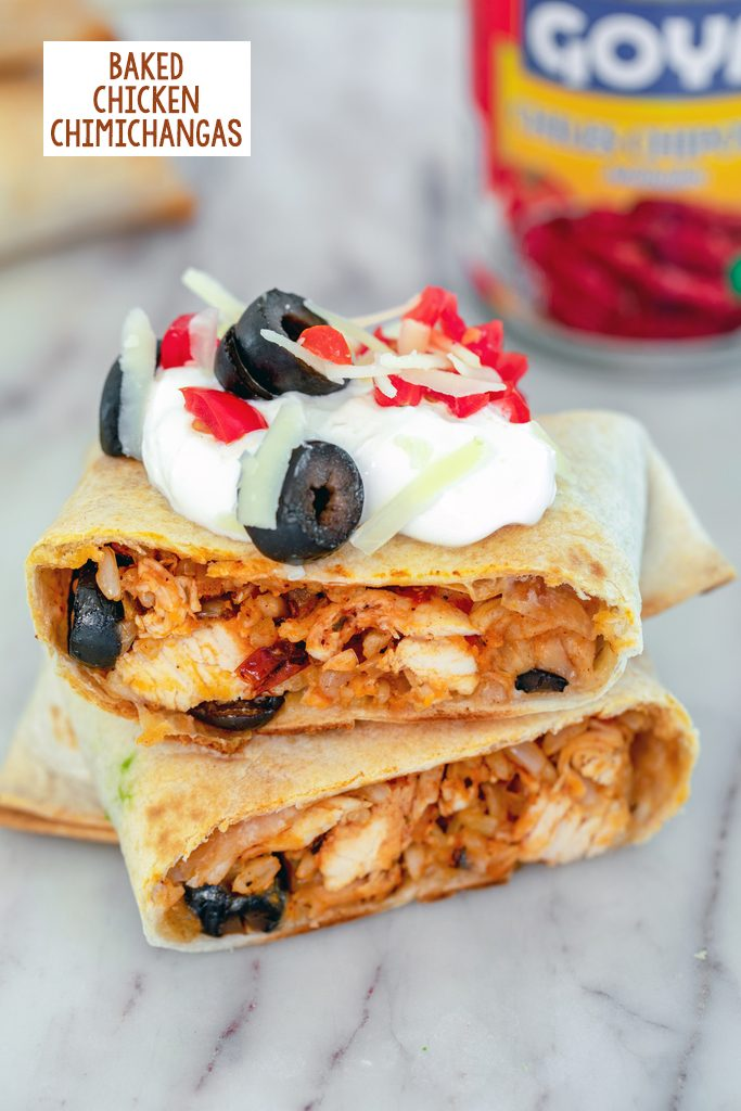 Head-on view of a baked chicken chimichanga cut in half and topped with sour cream, tomatoes, cheese, and olives, with can of chipotle peppers in background and recipe title at top