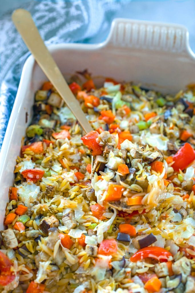 Overhead view of baked orzo with eggplant with lots of veggies and gold spoon taking out a scoop