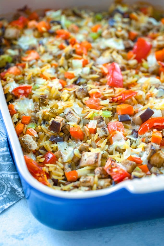 Head-on view of blue casserole dish filled with baked orzo with eggplant with lots of veggies