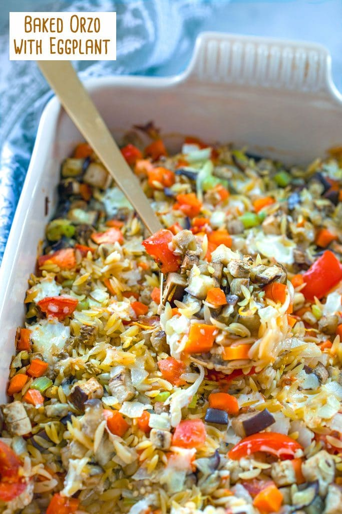 Overhead view of baked orzo with eggplant with lots of veggies and gold spoon taking out a scoop and recipe title at top