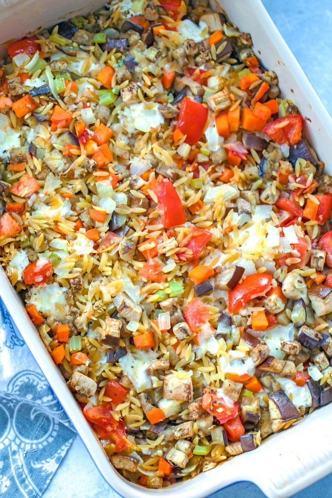 Overhead view of full casserole dish of baked orzo with eggplant with lots of bright veggies