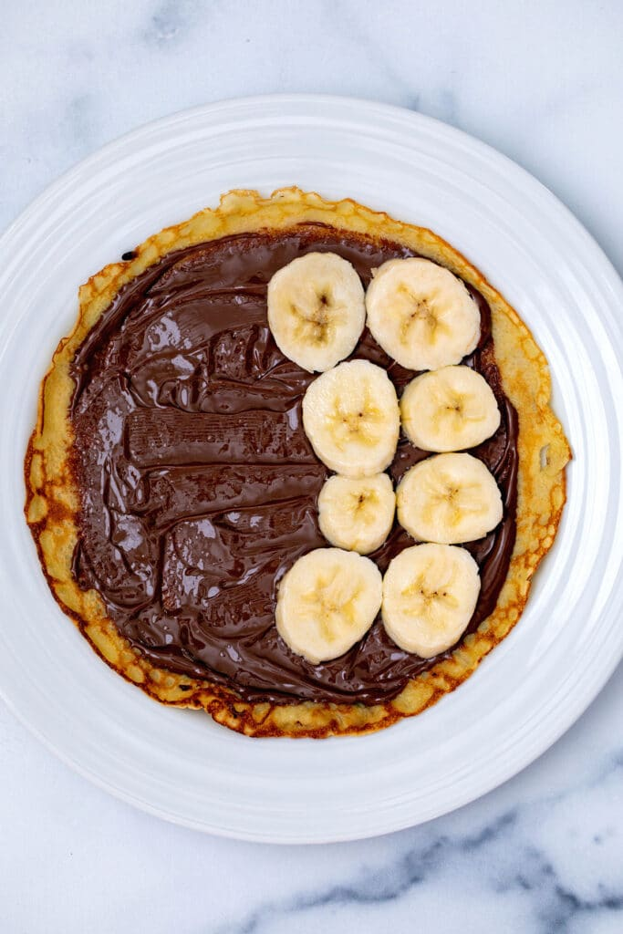 Overhead view a crepe on a plate with Nutella spread on it and bananas placed on it