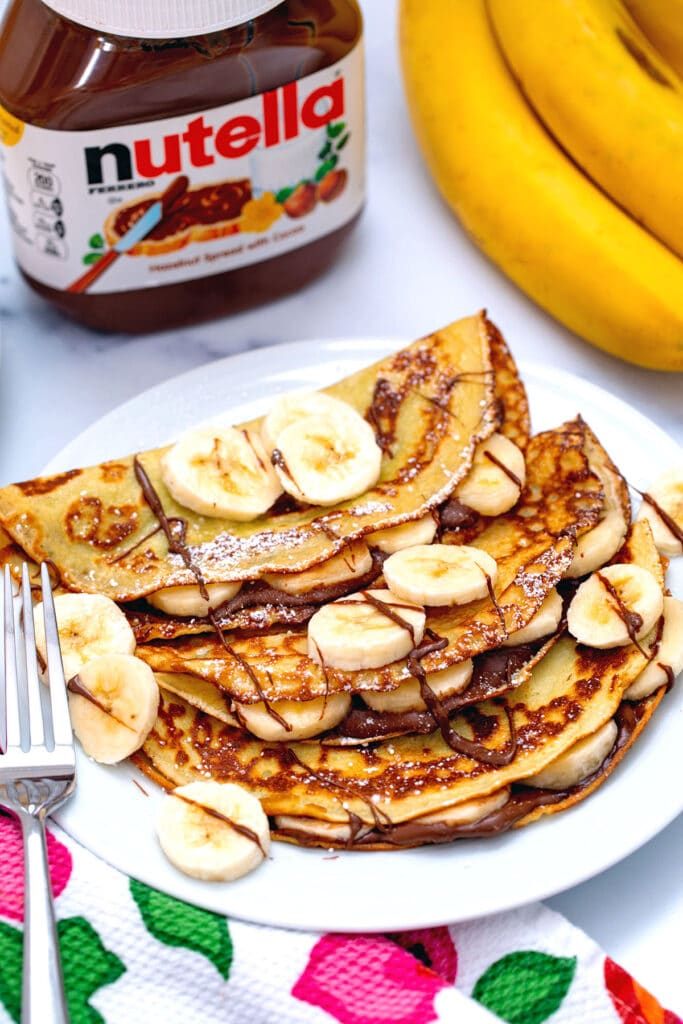 Three banana crepes on plate with Nutella drizzled on and sliced bananas on top with jar of Nutella and bunch of bananas in background