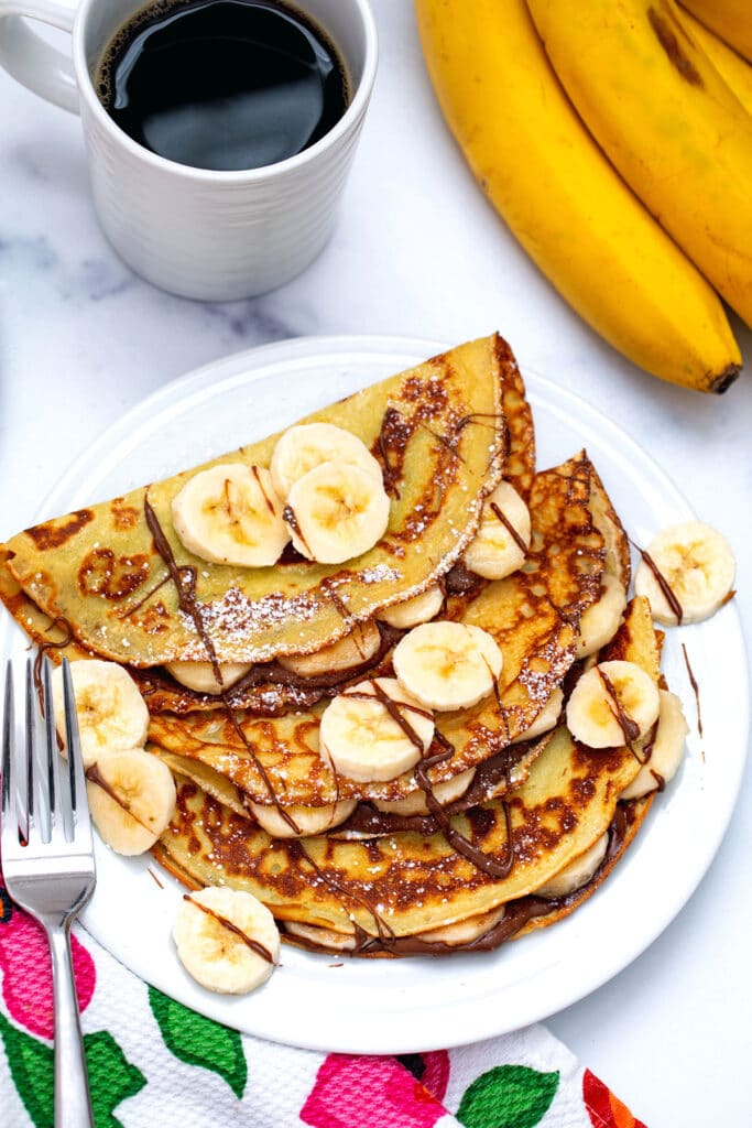 Bird's eye view of banana crepes on a plate with Nutella and sliced bananas with cup of cofee and bunch of bananas in background