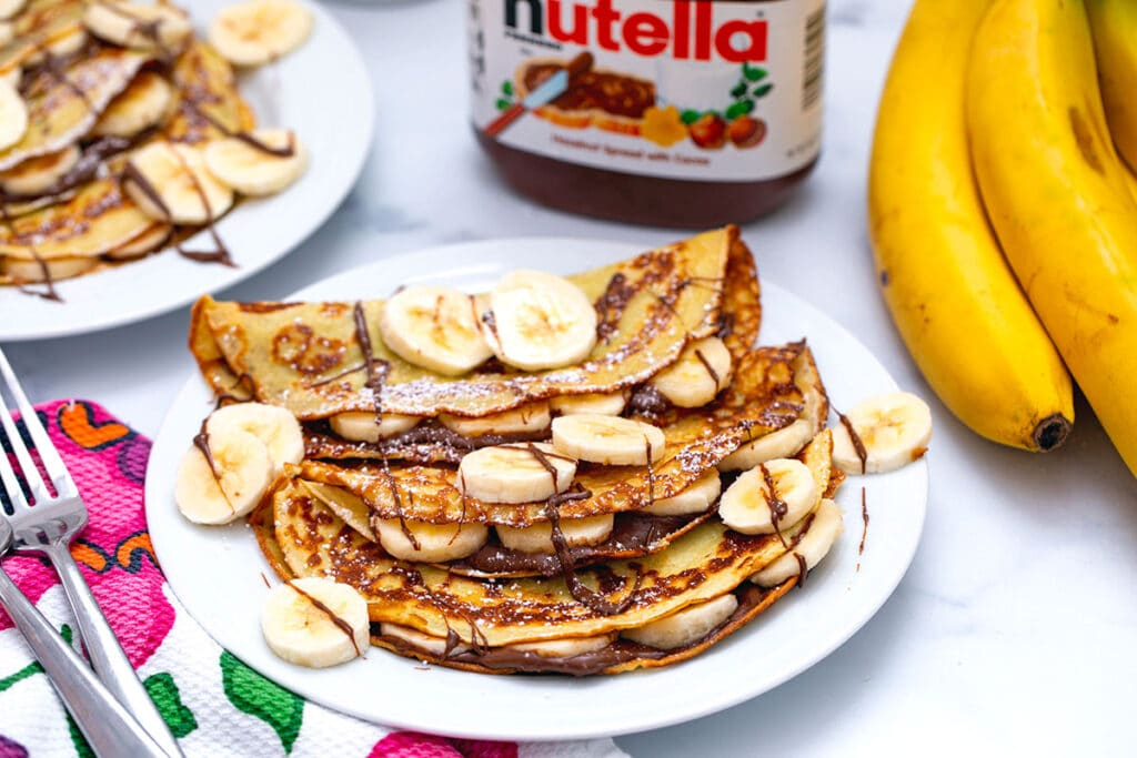 Landscape view of a plate of banana crepes with Nutella and sliced bananas with second plate, jar of Nutella, and bunch of bananas in background