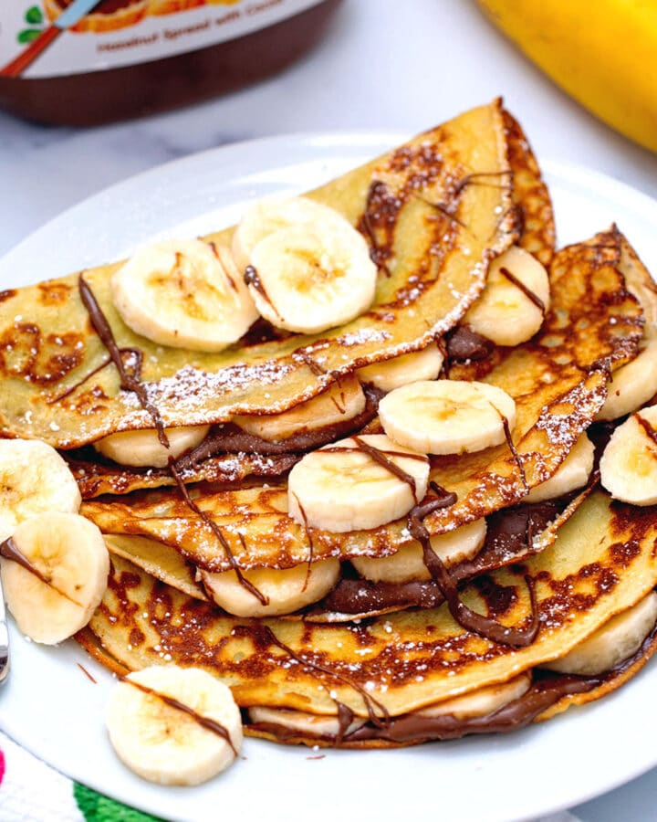 Three banana crepes on plate with Nutella drizzled on and sliced bananas on top