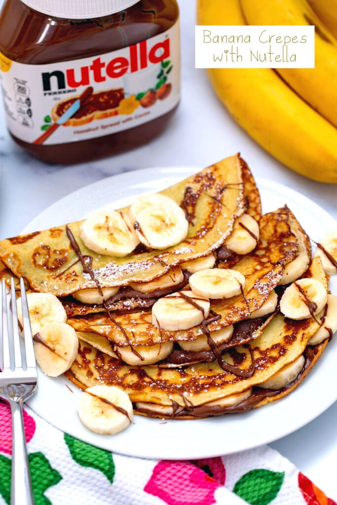 Three banana crepes on plate with Nutella drizzled on and sliced bananas on top with jar of Nutella and bunch of bananas in background and recipe title at top