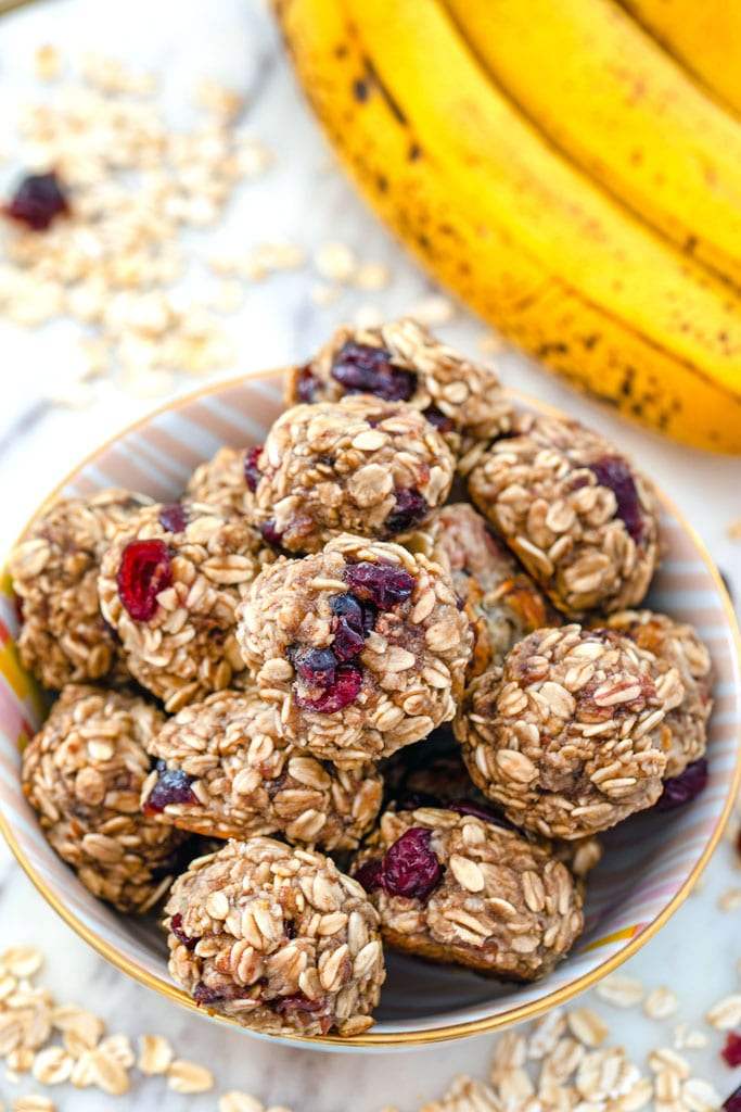 Overhead view of banana maple cranberry cookies in a bowl surrounded by oats and dried cranberries with bananas in background