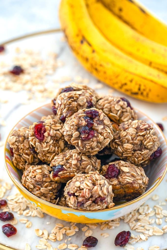 Head-on view of a bowl filled with banana maple cranberry cookies on a marble tray with oats and dried cranberries all around and bananas in background