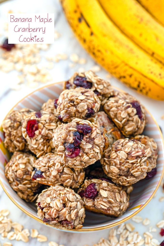 Overhead view of banana maple cranberry cookies in a bowl surrounded by oats and dried cranberries with bananas in background and recipe title at top