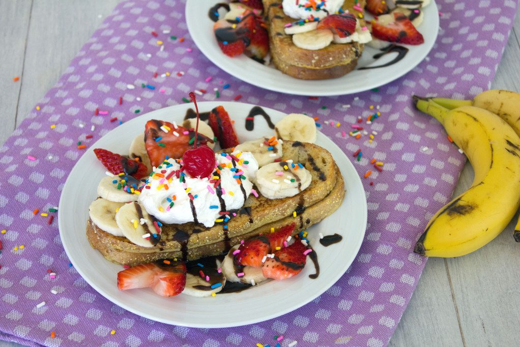 Landscape view of a plate of banana split french toast topped with bananas, strawberries, chocolate sauce, whipped cream, sprinkles, and a cherry with a second plate and whole bananas in the background