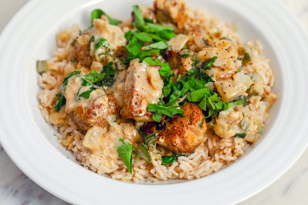 Landscape view of a white bowl filled with brown rice that's topped with basil chicken in coconut curry sauce with fresh basil on top