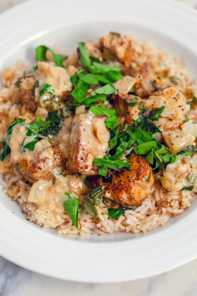 Overhead closeup view of a white bowl filled with brown rice and topped with basil chicken in coconut curry sauce with extra fresh basil on top