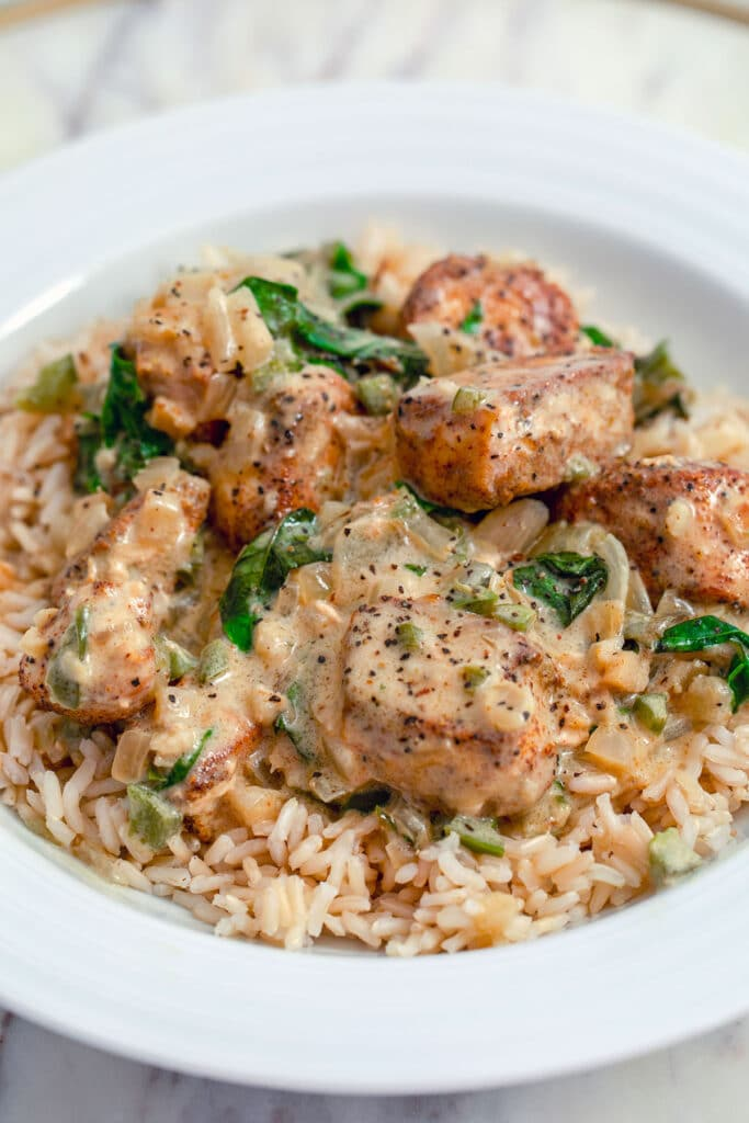 Head on view of basil chicken in coconut curry sauce sitting on a bed of brown rice in a white bowl
