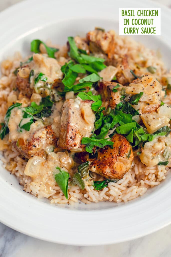 Overhead closeup view of a white bowl filled with brown rice and topped with basil chicken in coconut curry sauce with extra fresh basil on top and recipe title at top of image