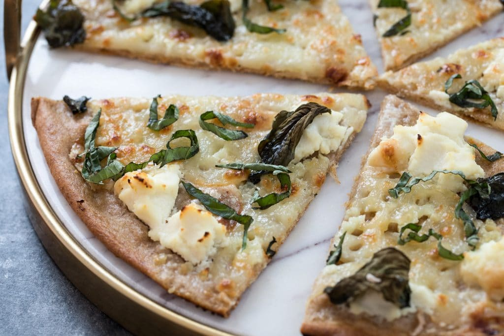 Landscape overhead view of multiple slices of basil and garlic white pizza on a marble tray
