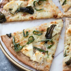 Basil and Garlic White Pizza -- Traditional pizza is always delicious, but there's something about a cheese-filled white pizza that really hits the spot. Add on a slathering of garlic oil and plenty of basil and you'll be in pizza heaven | wearenotmartha.com