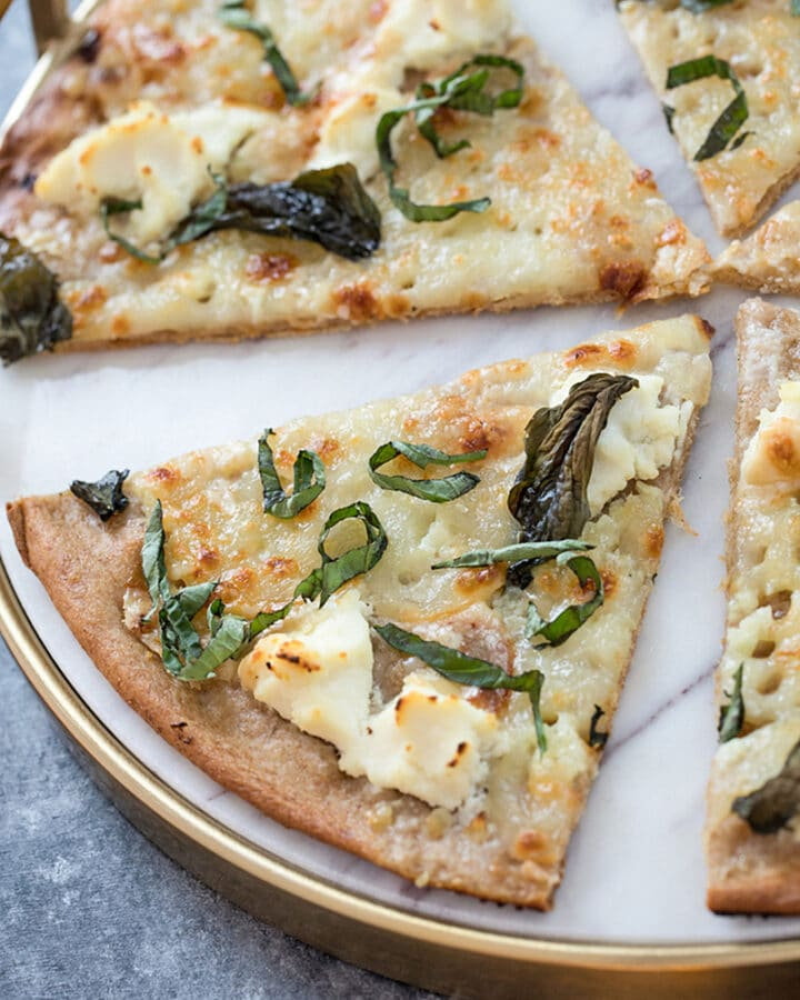 Basil and Garlic White Pizza -- Traditional pizza is always delicious, but there's something about a cheese-filled white pizza that really hits the spot. Add on a slathering of garlic oil and plenty of basil and you'll be in pizza heaven | wearenotmartha.com #pizza #whitepizza #wholewheatdough