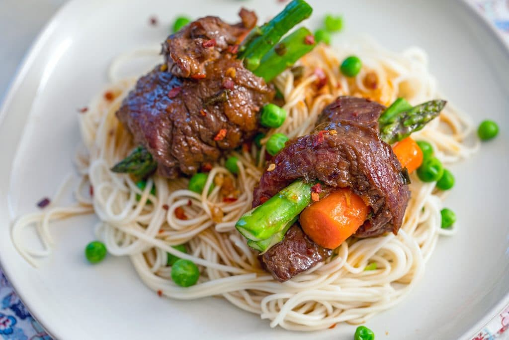 Landscape close-up view of steak-roll-ups with asparagus and carrots over a bed of noodles with peas