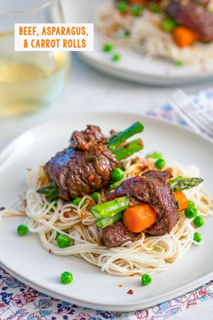 Head-on view of two steak roll-ups with asparagus and carrots over a bed of noodles and peas with a second plate and glass of white wine in the background with recipe title at top