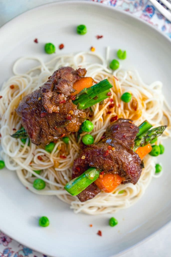 Overhead view of steak roll-ups with asparagus and carrots over a bed of noodles and peas