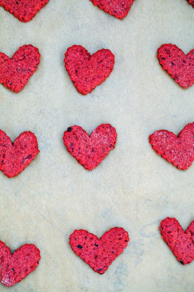 Heart-shaped beet cookies cut out on baking sheet