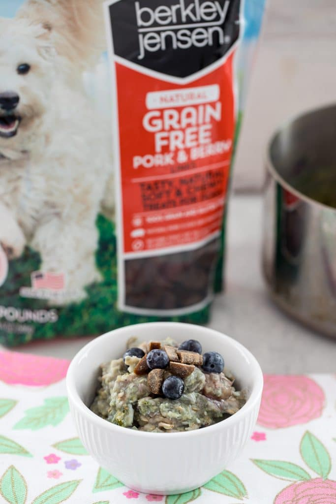 Shot of berry egg oatmeal for dogs in a white bowl with Pork and Berry Link treats in the background