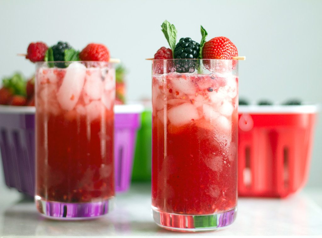 A head on view of two red berry cocktails with lots of ice and berry and mint garnishes