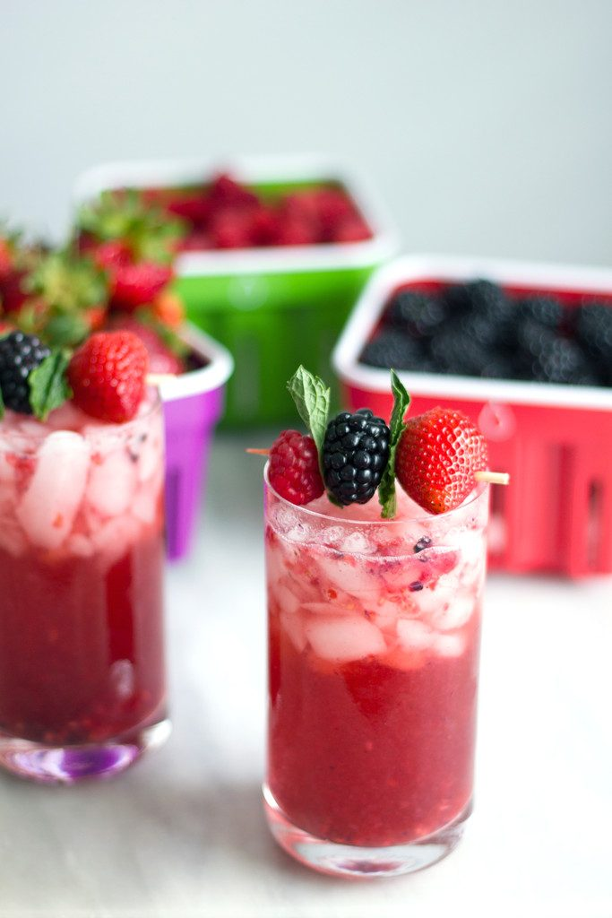 An arial view of two red berry cocktails with berry and mint garnishes and blackberries and raspberries in berry baskets in the background