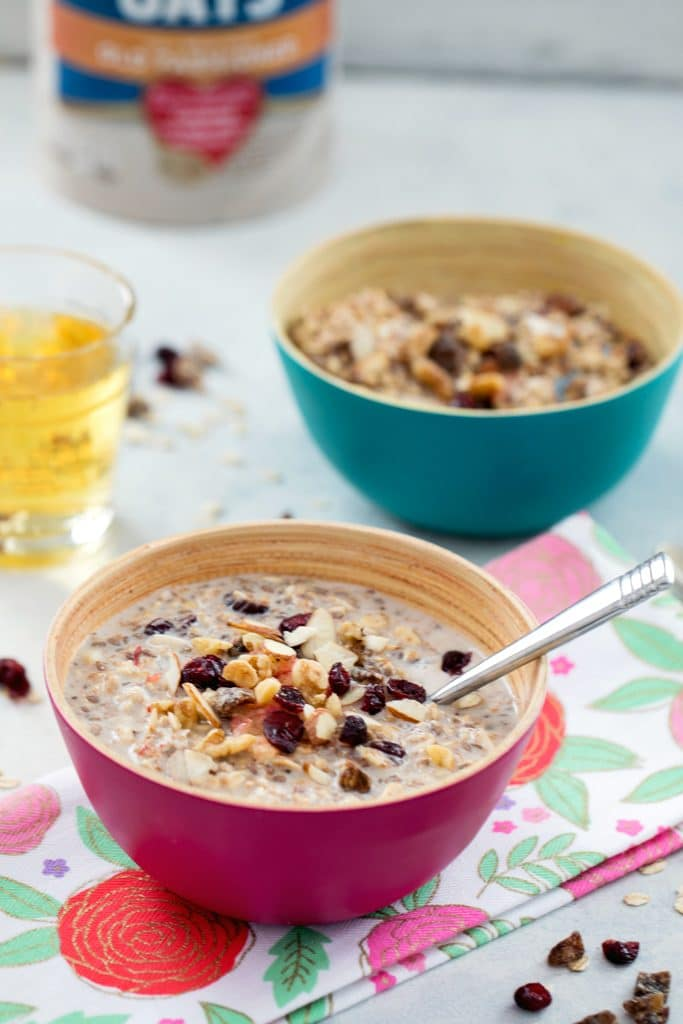 View from a distance of two bowls of bircher muesli topped with dried fruit with glass of apple juice, carton of oats, and dried fruit in the background