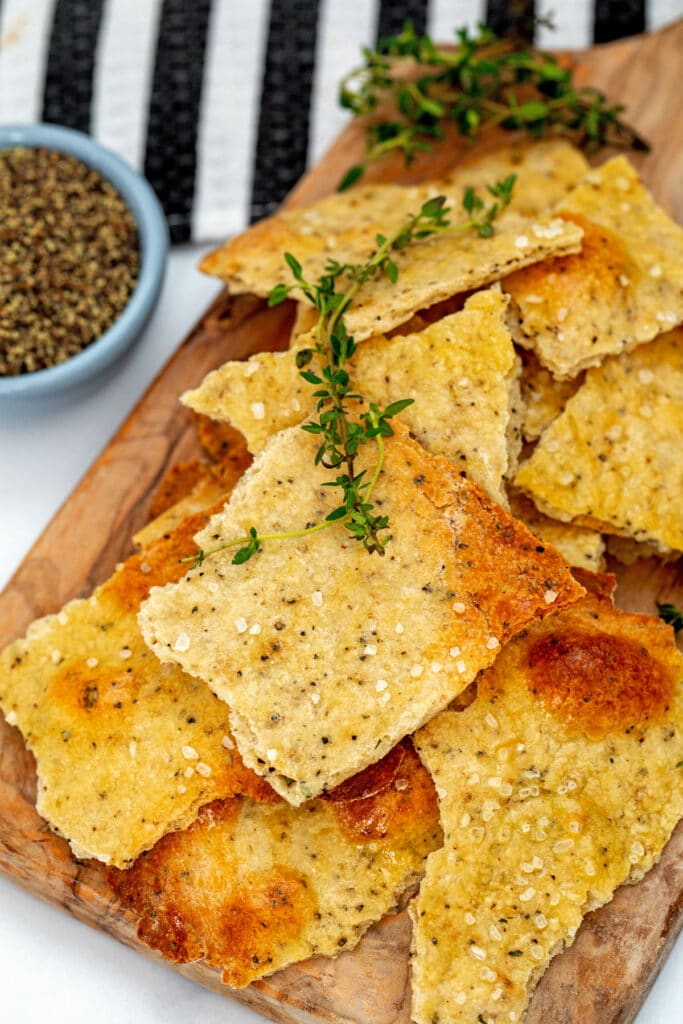 Closeup view of black pepper and thyme olive oil crackers with sprigs of thyme and small bowl of black pepper