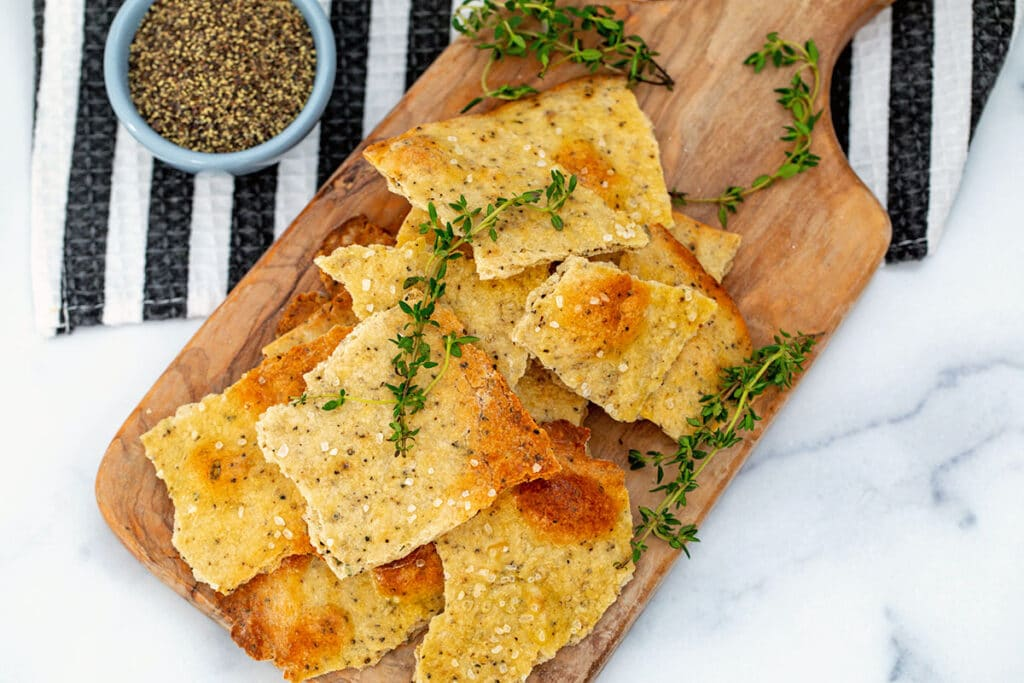 Landscape bird's eye view of black pepper and thyme olive oil crackers on a wooden board with sprigs of thyme and small bowl of pepper