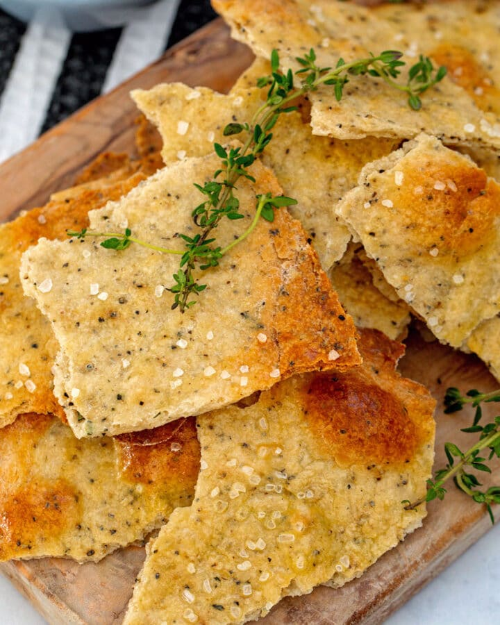 Overhead closeup of black pepper and thyme olive oil crackers on a wooden cutting board with sprigs of thyme