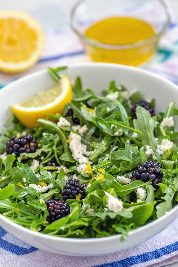 Head-on view of blackberry feta salad with arugula in a white bowl with lemon wedge and dressing and lemon in the background