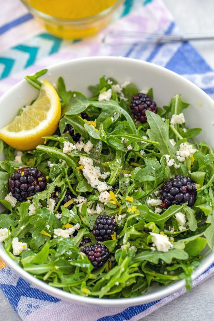Overhead view of blackberry feta salad with arugula and lemon wedge in a white bowl on a lavender napkin with yellow dressing and small whisk in the background
