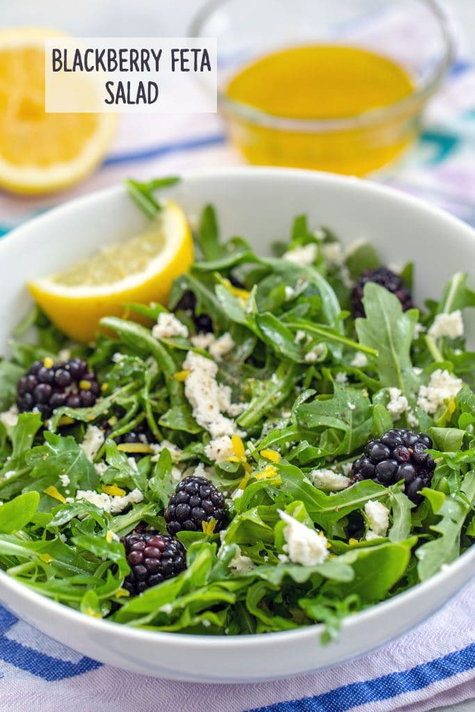 "Head-on view of blackberry feta salad with arugula in a white bowl with lemon wedge and dressing and lemon in the background and ""Blackberry Feta Salad"" text on top"