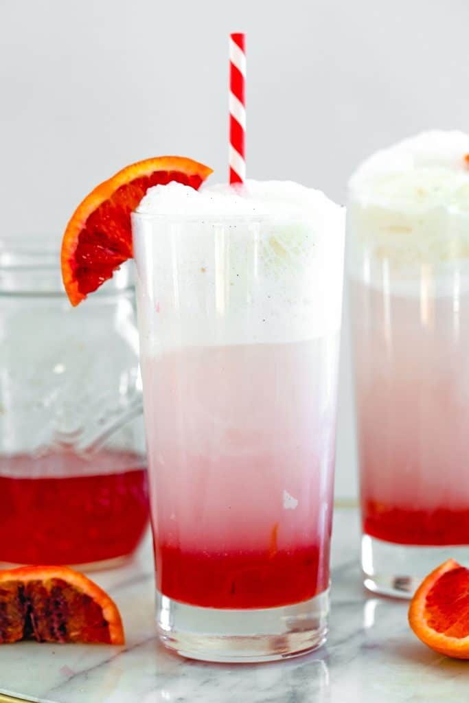 Head-on view of blood orange ice cream soda in a tall glass with red and white straw and blood orange wedge garnish with jar of simple syrup and second ice cream soda in the background