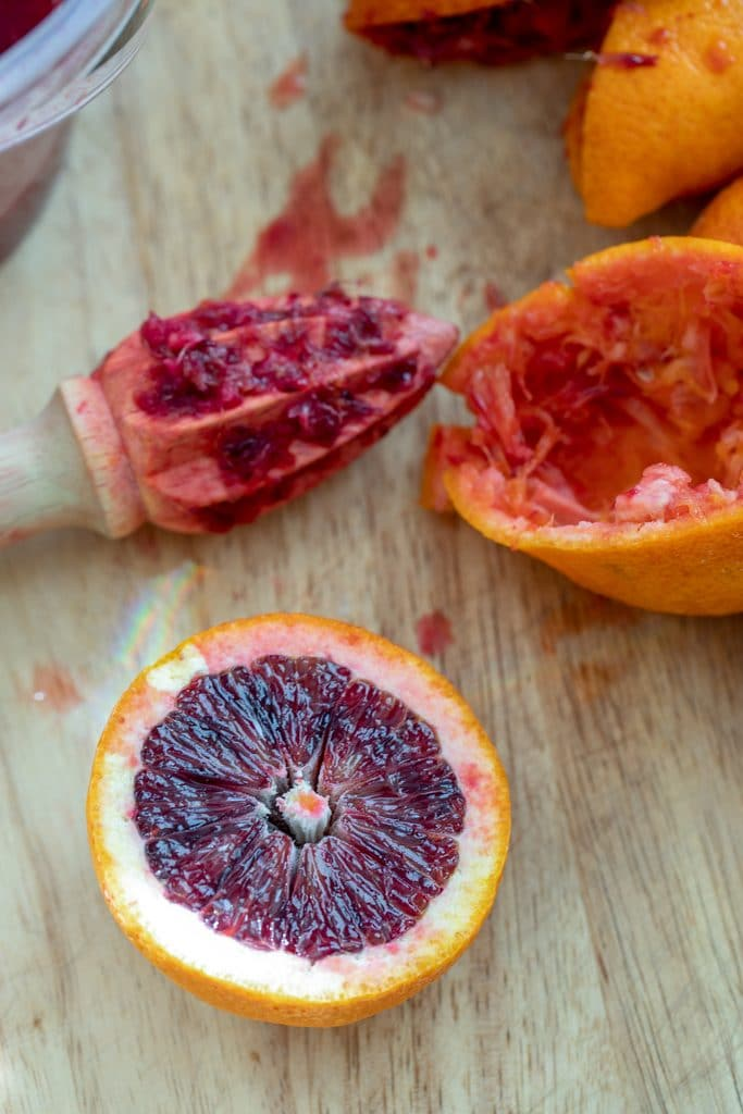 A blood orange half on a cutting board with citrus reamer and juice blood orange halves in the background