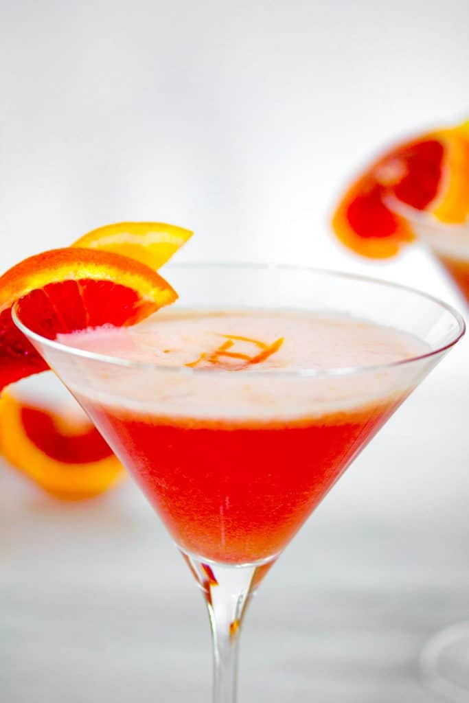 Close-up of the top of a blood orange meyer lemon gin sour in a martini glass with blood orange slice garnish and zest on top
