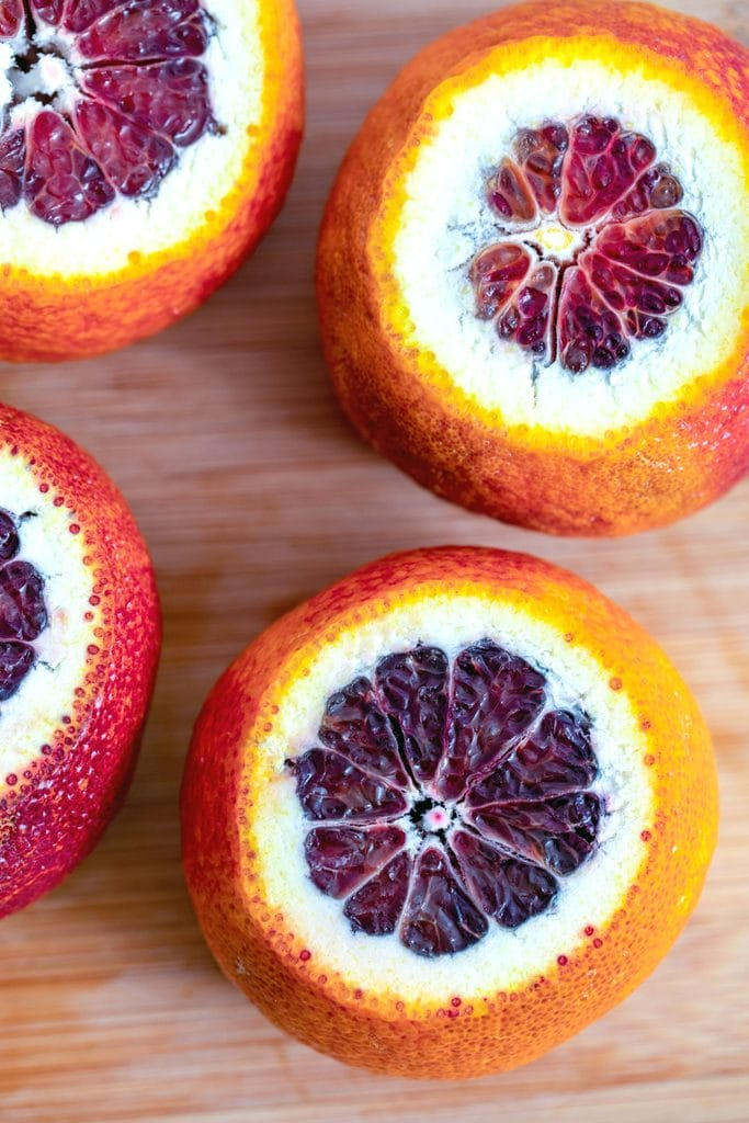 Overhead view of blood oranges with their tops and bottoms sliced off sitting on a cutting board