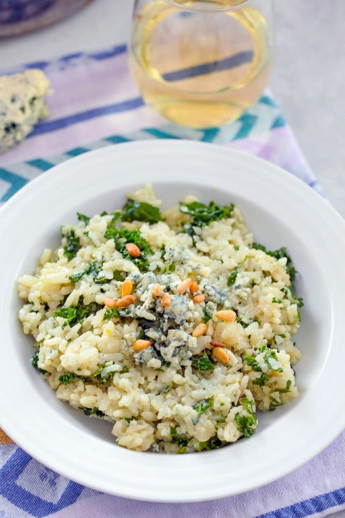 Overhead view of blue cheese risotto with kale topped with additional blue cheese and pine nuts with a glass of white wine and hunk of blue cheese in the background