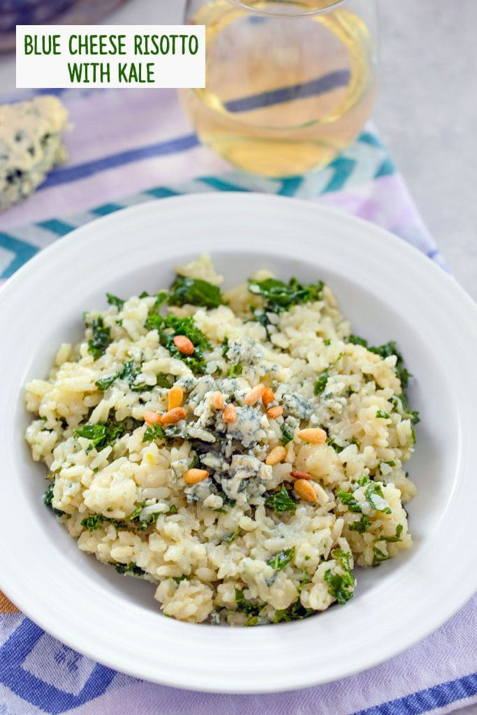 Overhead view of blue cheese risotto with kale topped with additional blue cheese and pine nuts with a glass of white wine and hunk of blue cheese in the background and recipe title at top