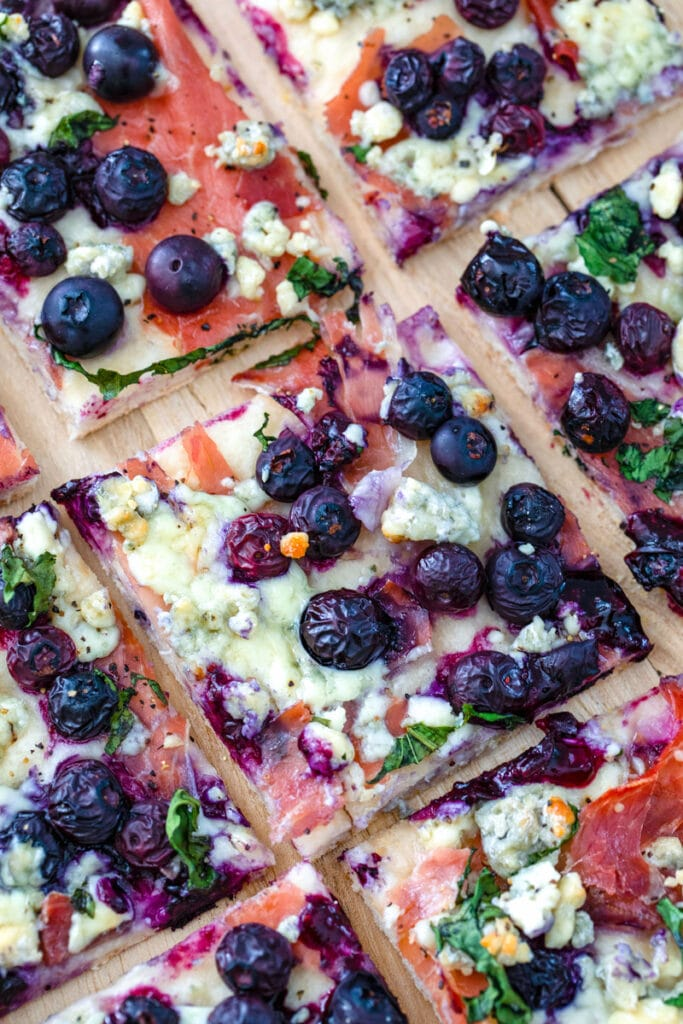 Closeup view of a square of blueberry blue cheese pizza on a cutting board